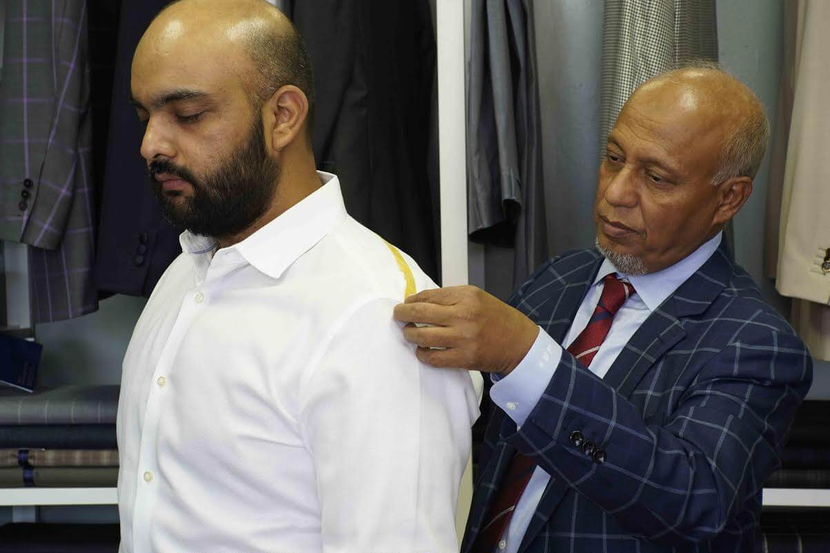 Mohammed Kalam taking measurements for a custom suit