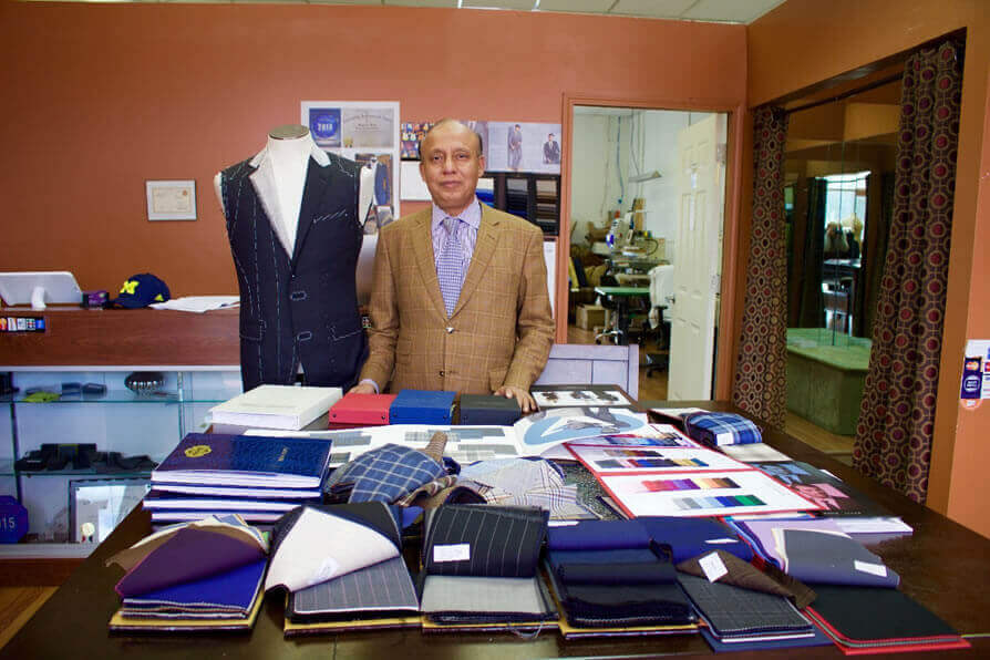 Mohammed Kalam showing off various suit fabrics