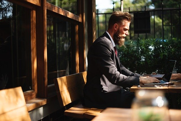 Man wearing a black suit sitting on an outdoor bench