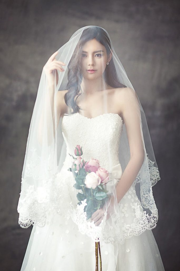 Wedding dress with veil and a bouquet of roses