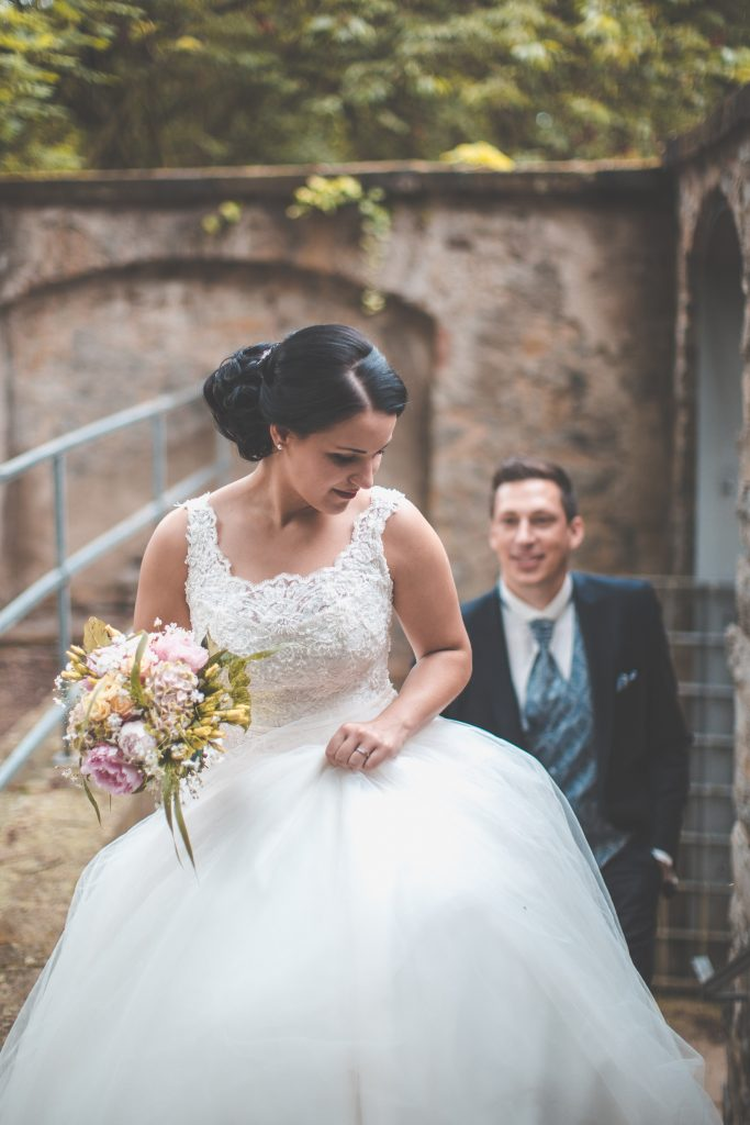 Woman in a wedding dress holding a bouquet and the groom posing at the back