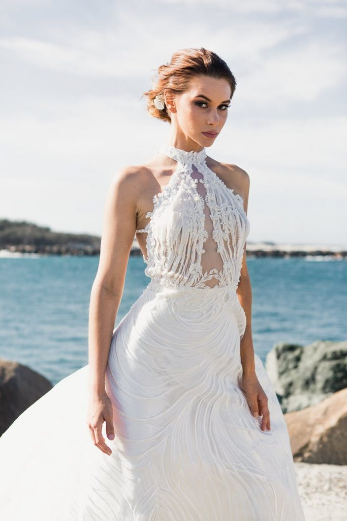 Woman on an elegant wedding dress near the sea