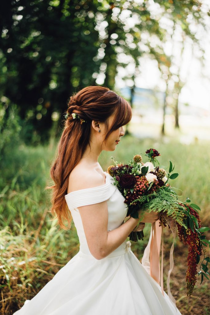 A woman on a wedding dress holding a bouquet outdoors